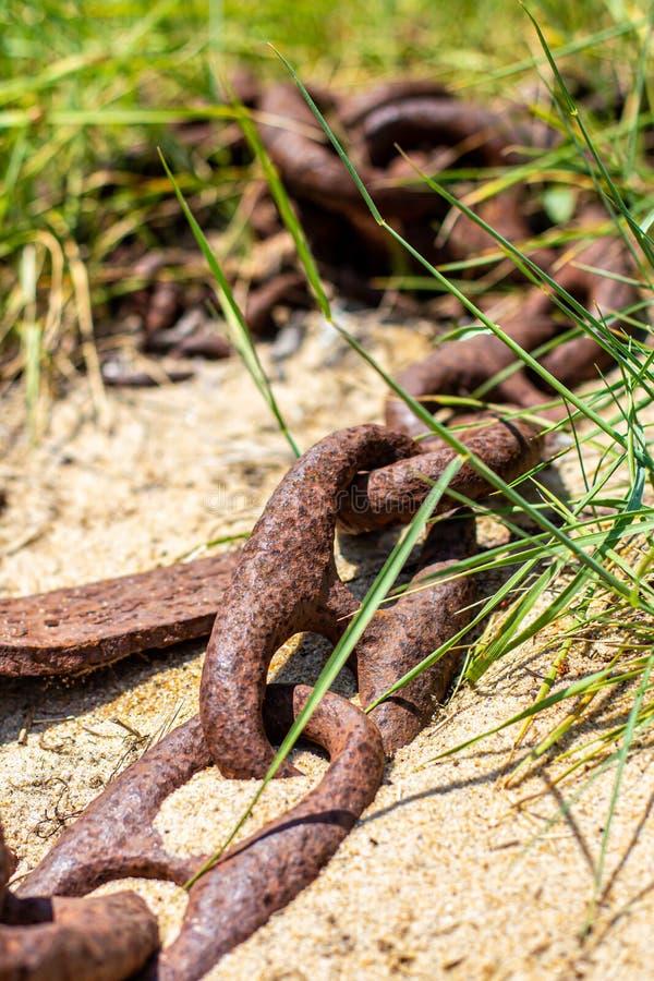 从一个小船船锚的生锈的链子在沙子 免版税库存照片
