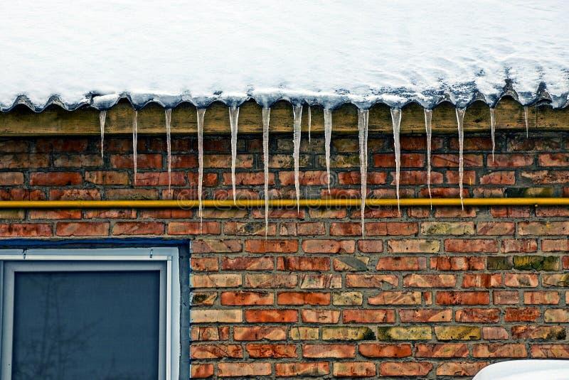 从一个屋顶的冰柱在有窗口的一个砖墙上 免版税库存图片