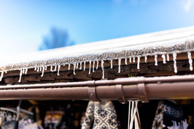 从一个木大厦在一冬天冷淡的天,在屋顶,可看见的塑料天沟的很多雪的屋顶的垂悬的冰柱和 免版税库存图片