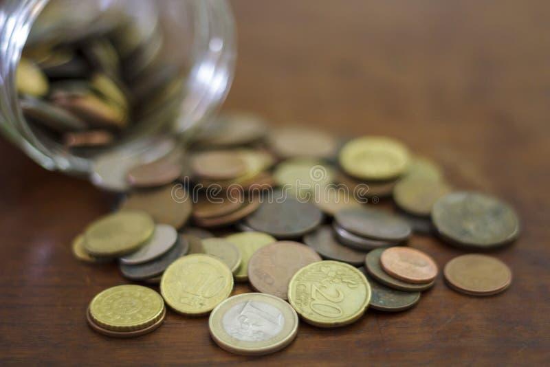 从一个玻璃瓶子溢出的硬币 免版税库存图片