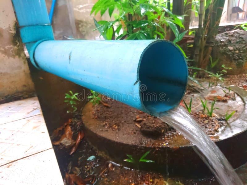 从一个蓝色管子的水流量 库存图片