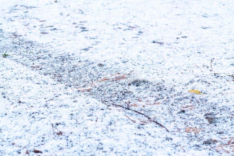 从一个车胎的轨道在第一降雪以后的石渣路 图库摄影