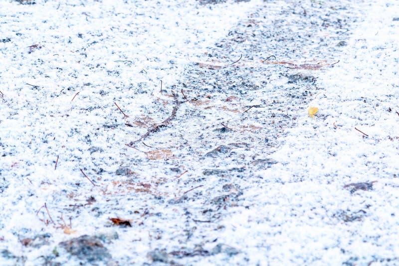 从一个车胎的轨道在第一降雪以后的石渣路 免版税库存图片