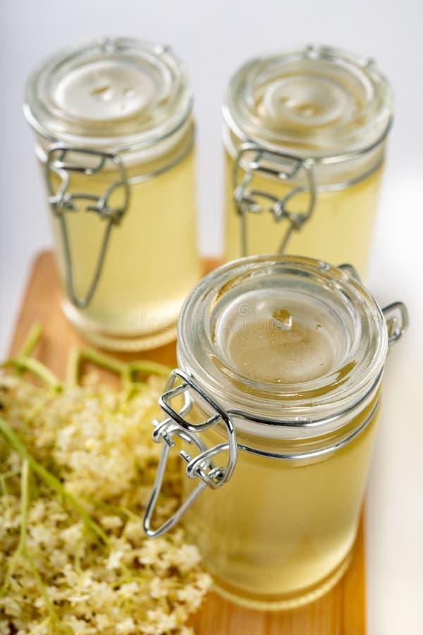 从一个黑接骨木浆果的花的汁液在一张白色桌上的 为存贮准备的治疗冷的糖浆的冬天 图库摄影
