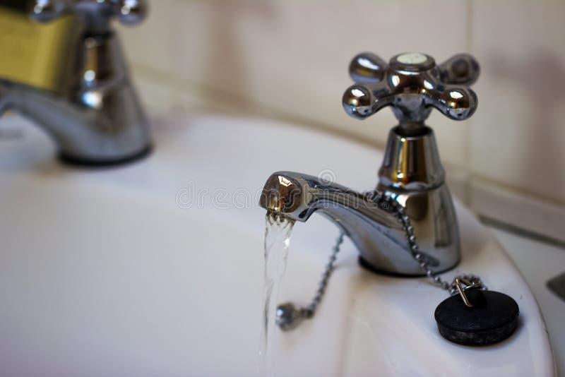 从一个龙头的自来水在卫生间里 库存图片