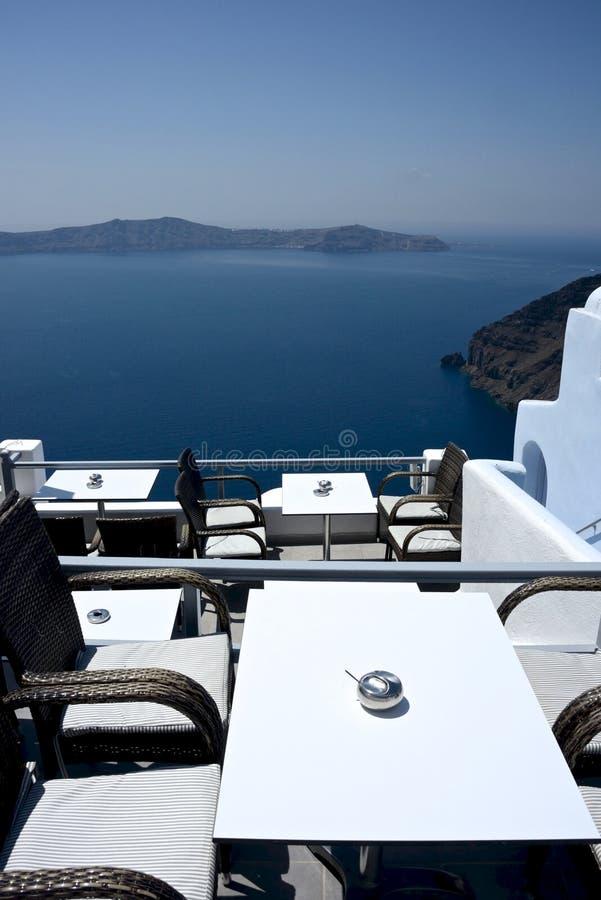 从一家室外大阳台餐馆的全景海滨人行道视图有现代椅子和桌的 库存图片