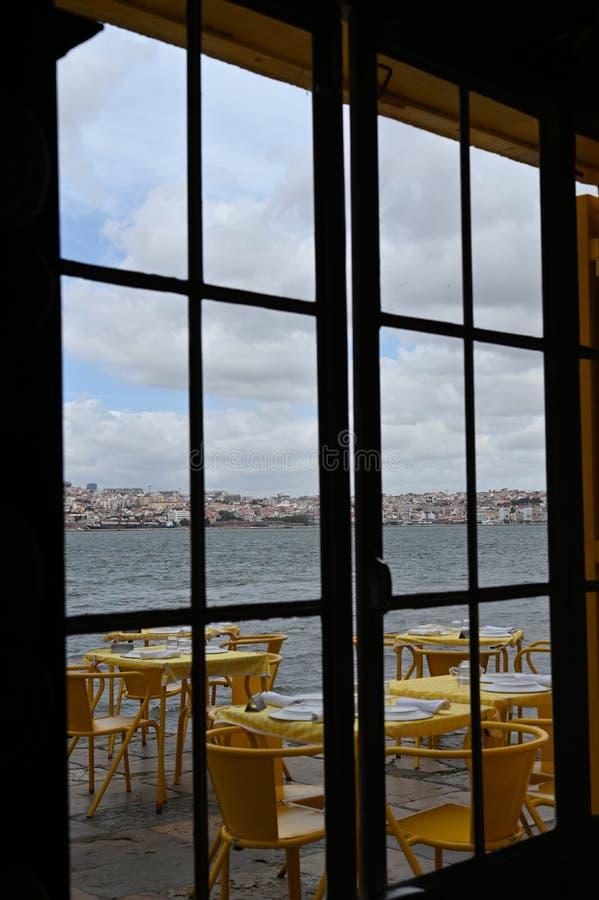 从一家餐馆的黄色桌的窗口的看法一个老码头的在田乡河在里斯本 免版税图库摄影