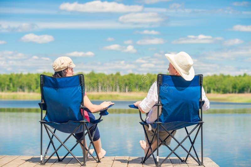 从一对夫妇的后面看法在椅子放松 库存图片