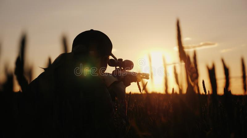 从一杆步枪的狙击步枪有瞄准具的 在日落 射击和寻找概念的体育 免版税图库摄影