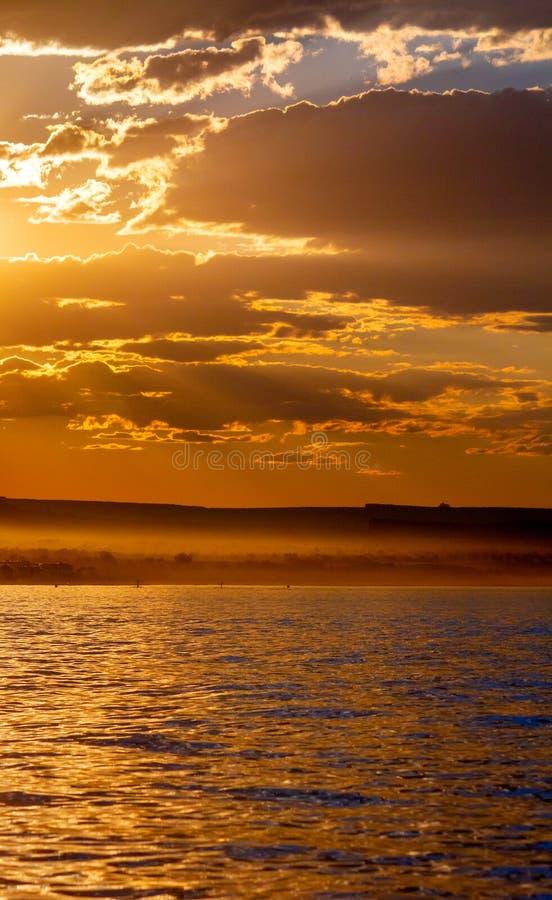 从一条土路的尘土由露营地在日落光发光由孤立岩石在湖鲍威尔 库存照片