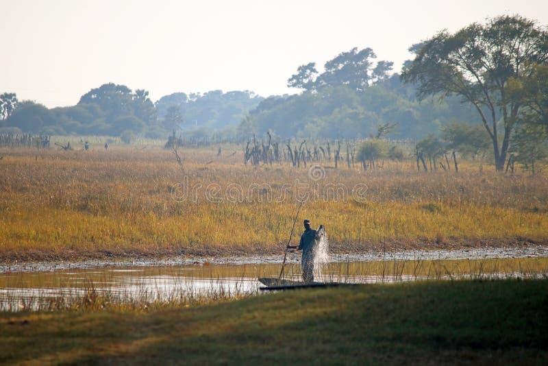 从一条小船的地方渔夫掩网在一条河在非洲 库存照片