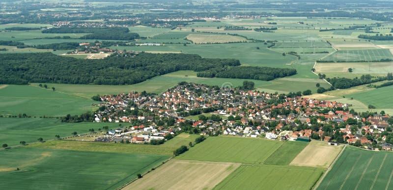 从一架小飞机的鸟瞰图从在不伦瑞克附近的一个村庄有领域、草甸、农田和小森林的在区域 图库摄影