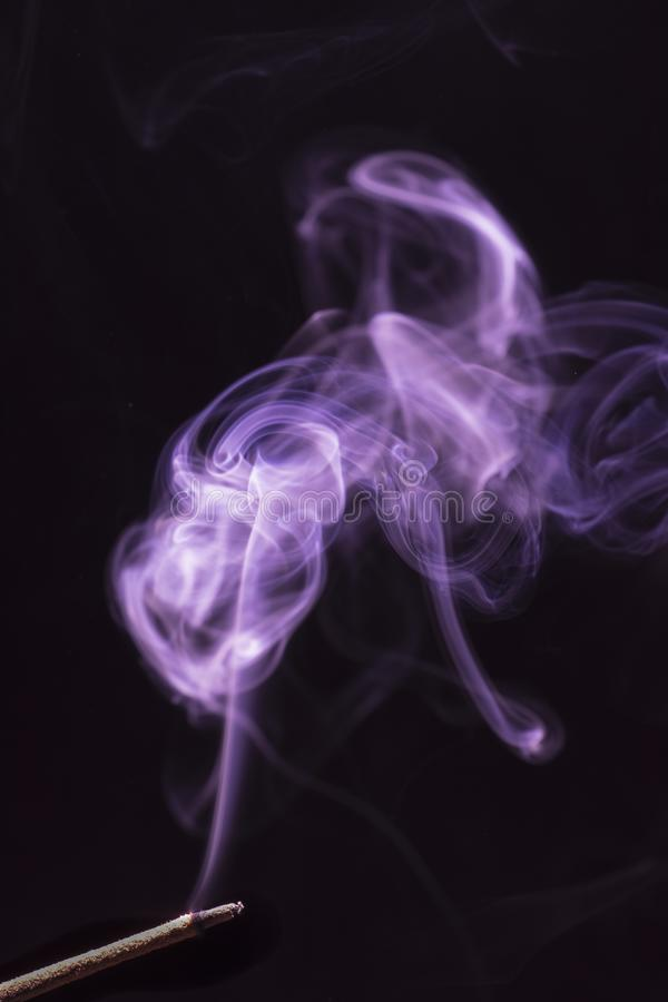 从一根灼烧的香火棍子的美丽的紫色和白色烟 图库摄影
