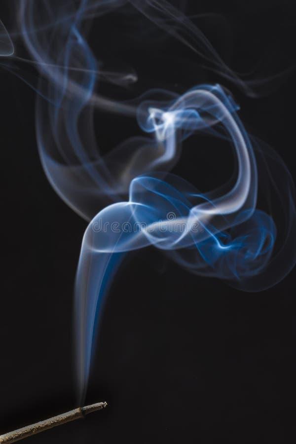 从一根灼烧的香火棍子的美丽的蓝色和白色烟 免版税库存图片