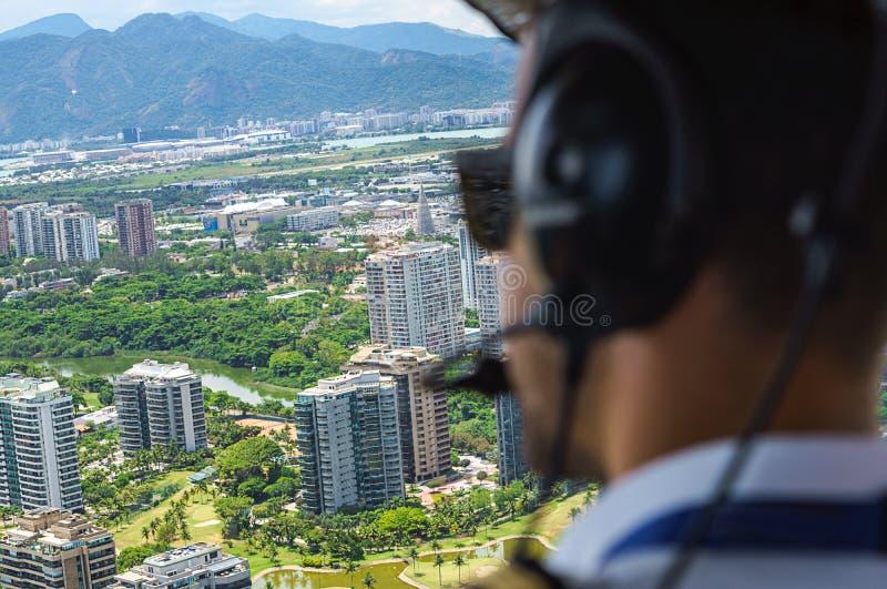 从一次直升机驾驶舱飞行的看法在里约热内卢 与飞行员和控制板的驾驶舱在客舱里面在一好日子 免版税库存图片