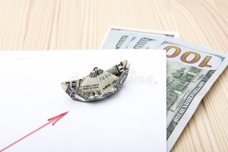 ?? 从一美元折叠的小船举行在日程表的方式 库存照片