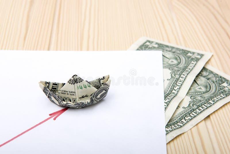 ?? 从一美元折叠的小船举行在日程表的方式 库存图片