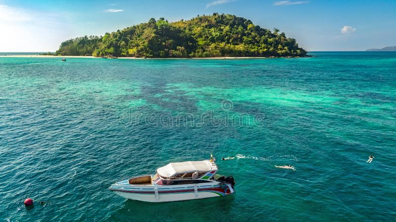 从上面潜航在清楚的热带海、空中寄生虫视图,母亲和游泳在水中的孩子snorkelers的小船附近的家庭 库存图片