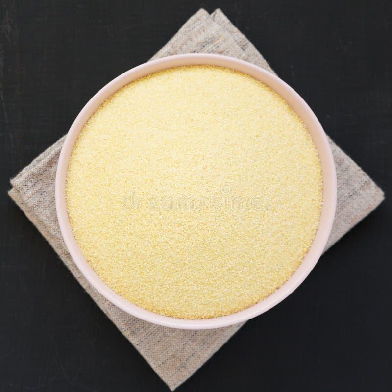 从上面,在一个桃红色碗的干粗面粉硬粒小麦面粉在黑表面,顶视图 r r 免版税图库摄影