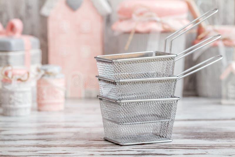 从不锈钢的油炸物篮子在装饰Kitchenw前面 免版税库存图片