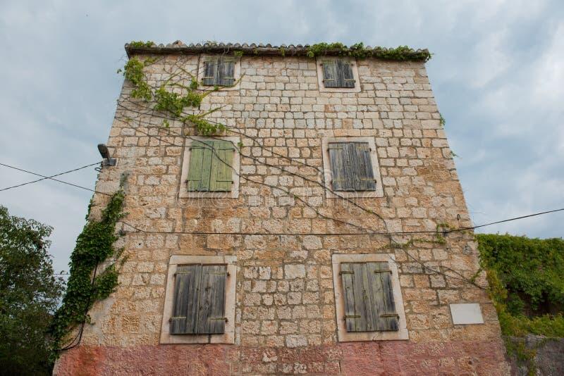 从与闭合的木窗口的石头做的老和被放弃的房子 与云彩的蓝天在背景中 葡萄酒海房子 免版税库存图片