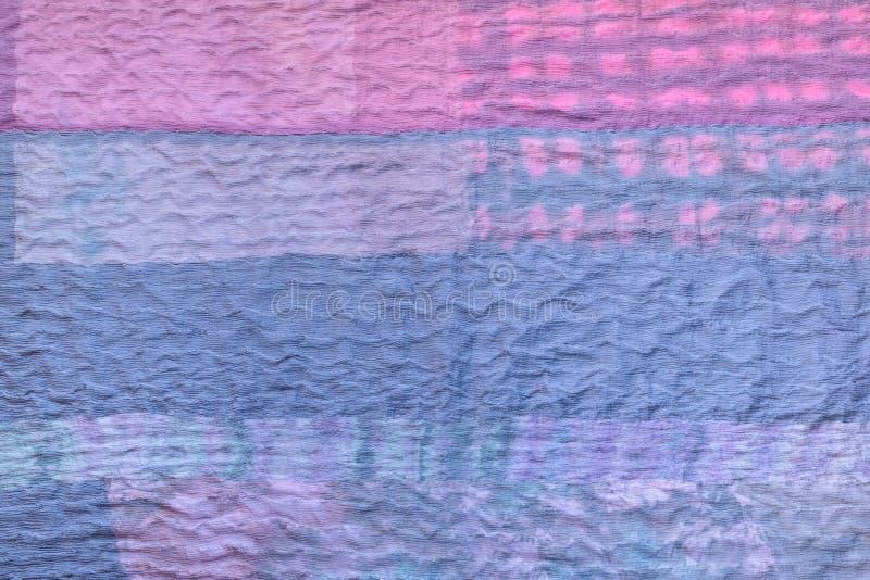 从丝绸被缝的围巾的蓝色纺织品背景 免版税库存图片