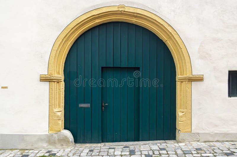 从中世纪的田园诗和美妙地被恢复的庄园与有半圆拱和固定门的一个大绿色木门 库存照片