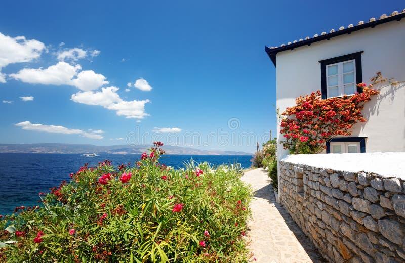 从九头蛇海岛的看法 传统希腊房子 帝堡城九头蛇和Kamini海滩 与软的白色云彩的天空蔚蓝 免版税库存图片