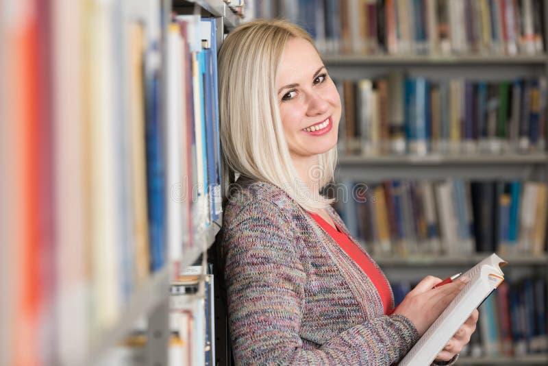 从书的愉快的女学生读书在图书馆里 免版税库存照片
