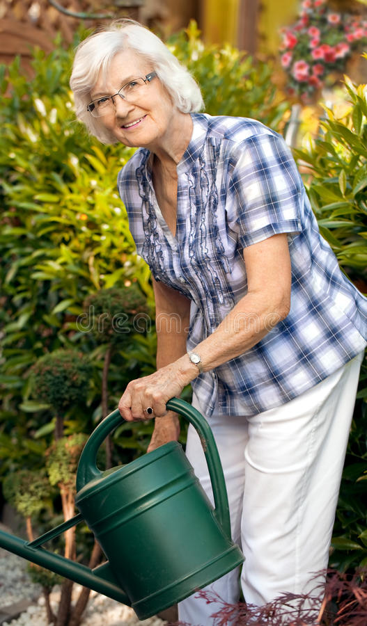 从事园艺她的高级浇灌的妇女 库存照片
