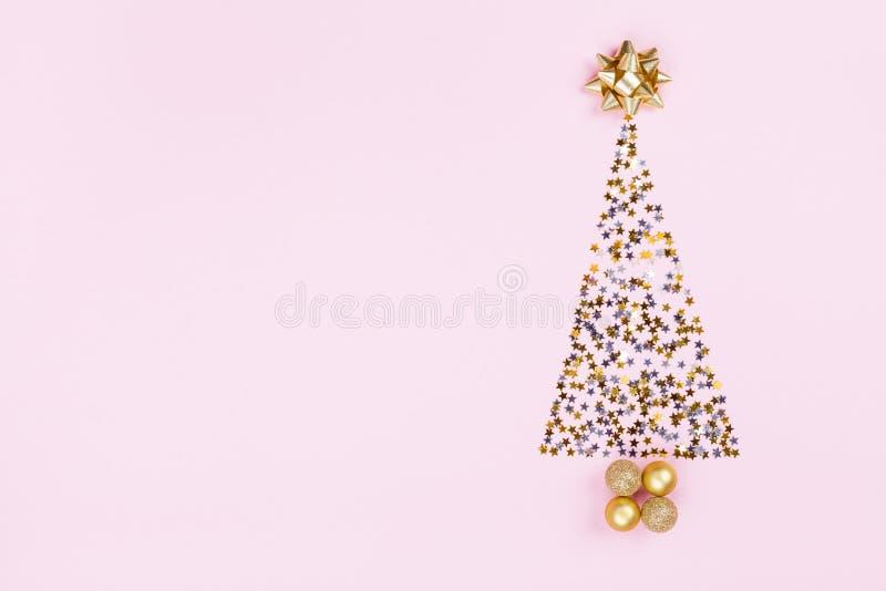 从五彩纸屑星,蜒蜒和金黄球的圣诞节创造性的杉树在桃红色背景顶视图 平的位置 免版税库存图片