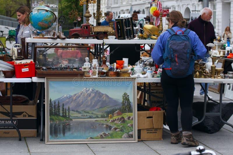 从人们卖并且买使用的玩具、衣裳、图片、厨房商品和其他葡萄酒事的跳蚤市场的场面 图库摄影