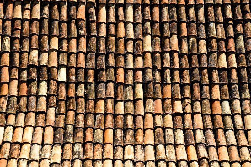 从传统老房子屋顶的细节有老棕色陶瓷砖的,损坏和用完由对元素的暴露 图库摄影