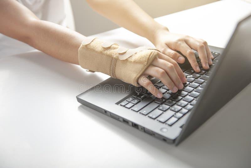 从使用计算机的腕子痛苦,办公室综合症状手痛苦或者伤害 免版税库存照片