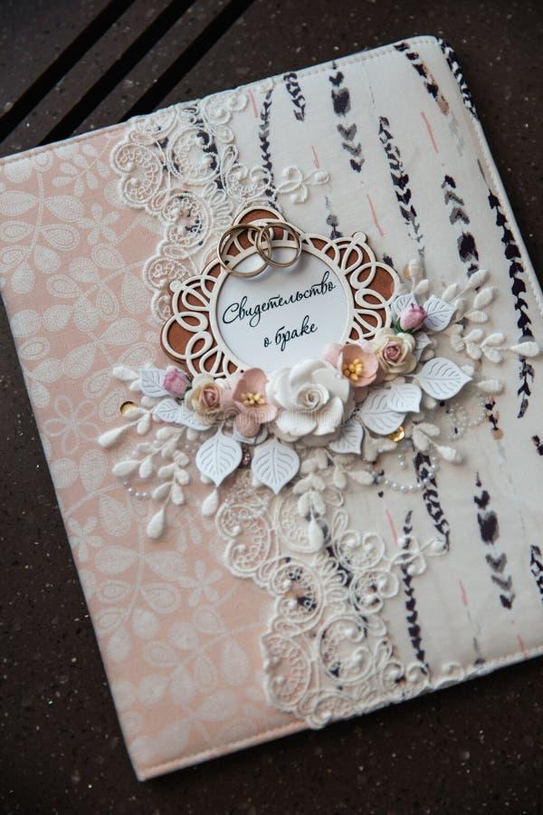 从俄语翻译的结婚证书的美妙地装饰的对此投入的书和结婚戒指-花 库存图片
