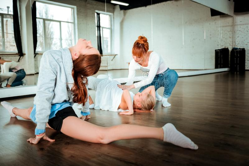 从做舒展的一代z的两个少年锻炼在他们的老师控制下 库存图片