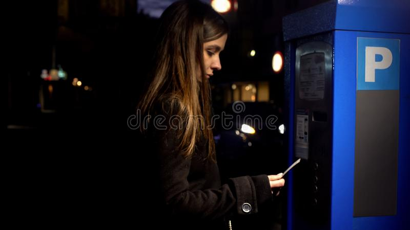 从停放的付款机器的夫人买的票在晚上,罪行风险,危险 免版税库存照片