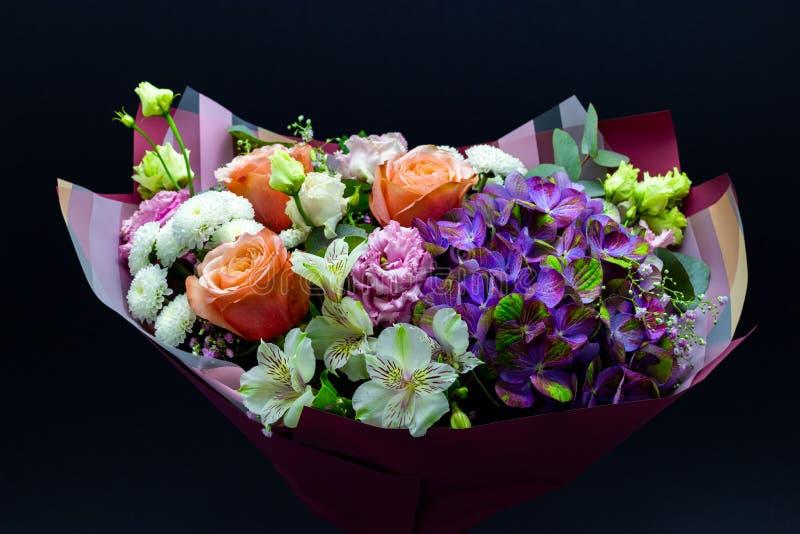 从八仙花属、牡丹玫瑰、菊花、南北美洲香草和德国锥脚形酒杯装配的明亮的不同的花束 免版税库存图片