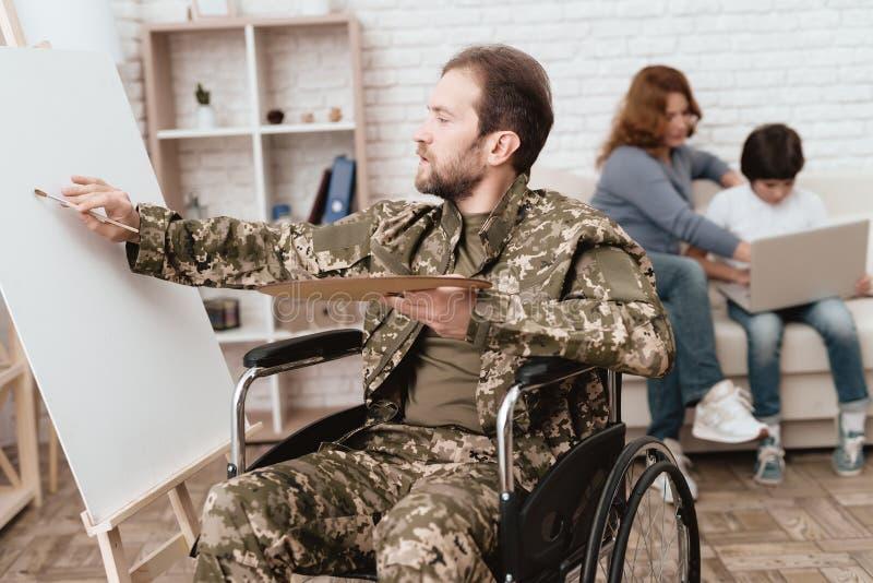 从军队返回的轮椅的退伍军人 轮椅的人画 人举行油漆和刷子 库存照片