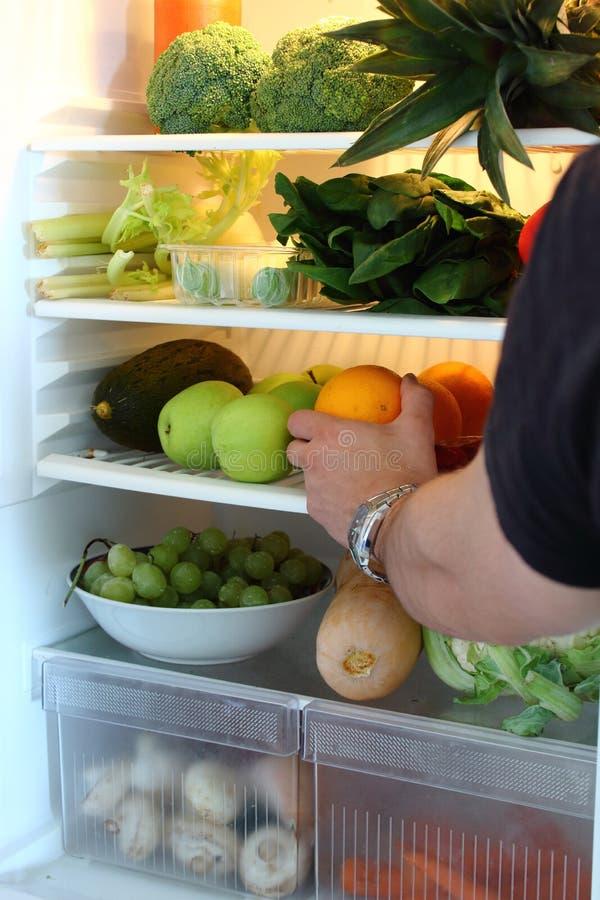 从冰箱的男性手采摘食物 库存图片