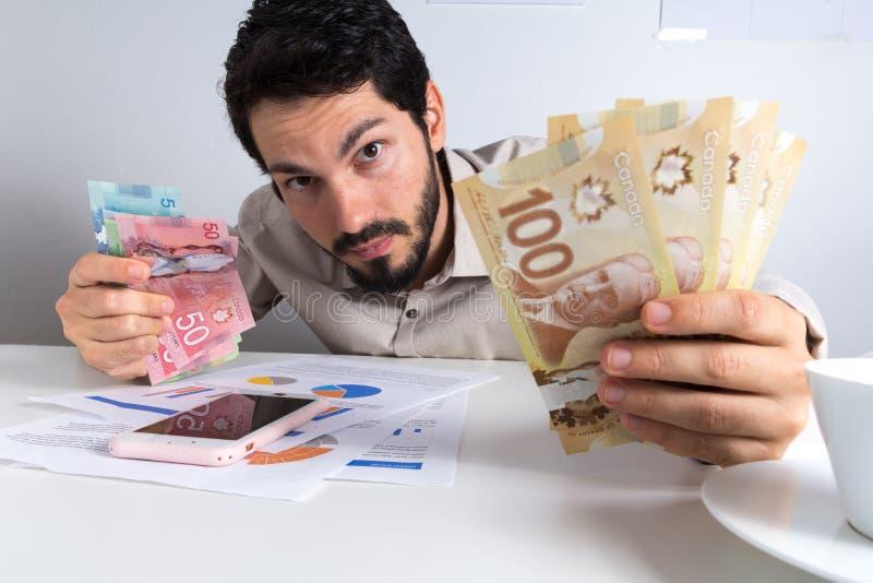 从加拿大的纸笔记 美元 拿着在桌上的年轻成人许多票据 库存照片