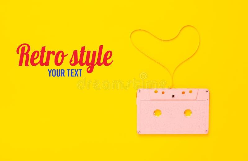 从卡型盒式录音机磁带的心脏形状在黄色纸背景,顶视图 行家爱 库存照片