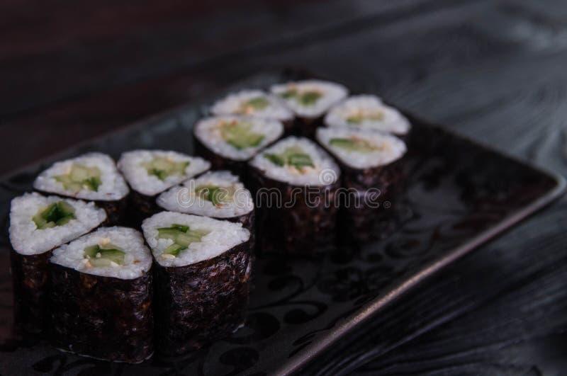 从卷在一块黑石板材的maki寿司开花 新鲜做寿司设置用乳酪和黄瓜 库存照片