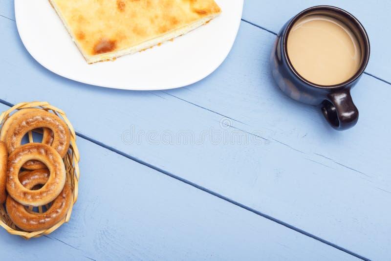 从可口部分甜点点心的甜开胃菜 热的茶或咖啡和cnack在白色板材和在木桌上 库存照片