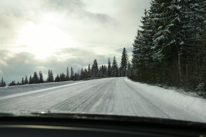 从司机` s位子的看法在用雪盖的路,强的blindi 图库摄影