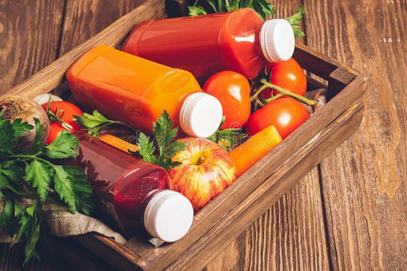 从各种各样的菜红萝卜苹果蕃茄甜菜瓶的新鲜的汁液圆滑的人在木箱褐色背景中 免版税库存照片