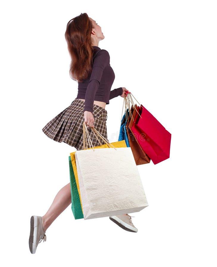 从后景看一个女人跳着购物袋 库存图片