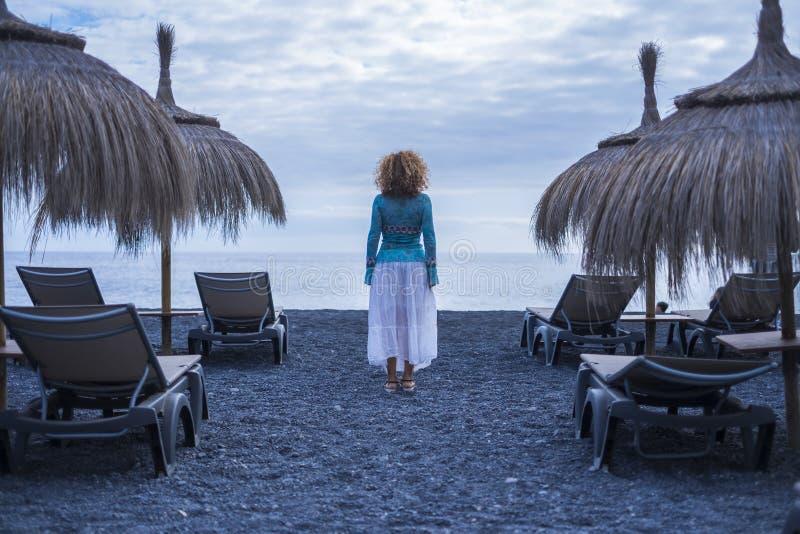 从后部立场观看的孤独的妇女在等待和看安静的海洋的空位进去和阳伞中间 免版税库存照片