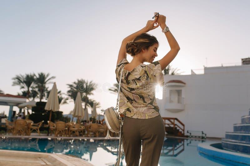 从后面妇女的看法获得乐趣,享受时间在美丽的水池附近,在温泉旅馆,手段,假期,假日,跳舞 图库摄影