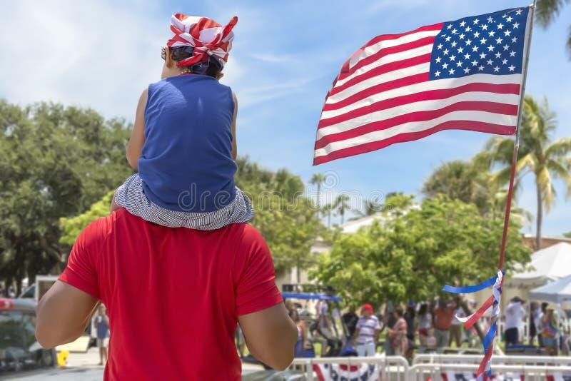 从后面父亲运载他的他的肩膀的年轻儿子庆祝有社区的美国人 图库摄影